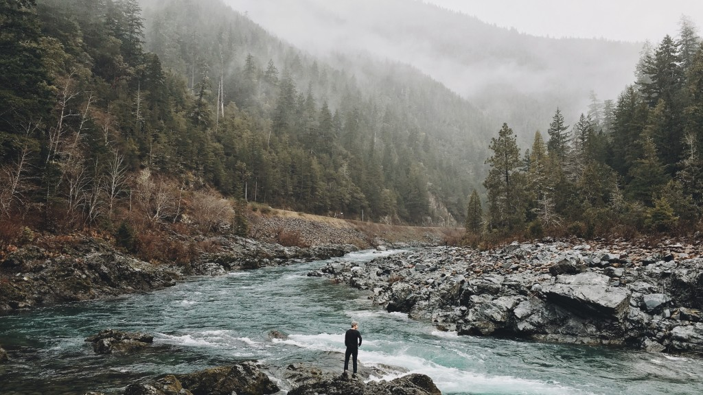 Man stands by the edge of the water.  Landscape of a mountain stream.